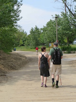 Walk-a-thon participant and sighted guide walking along the boardwalk.