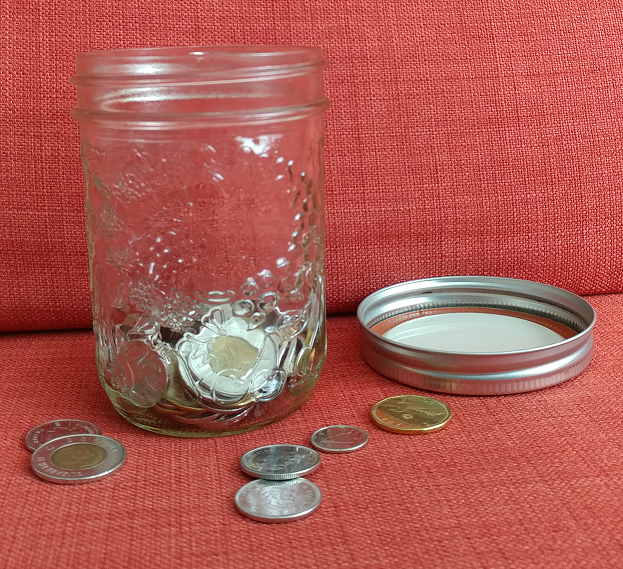 A jam jar with Canadian coins inside, lid is to the right of the jar