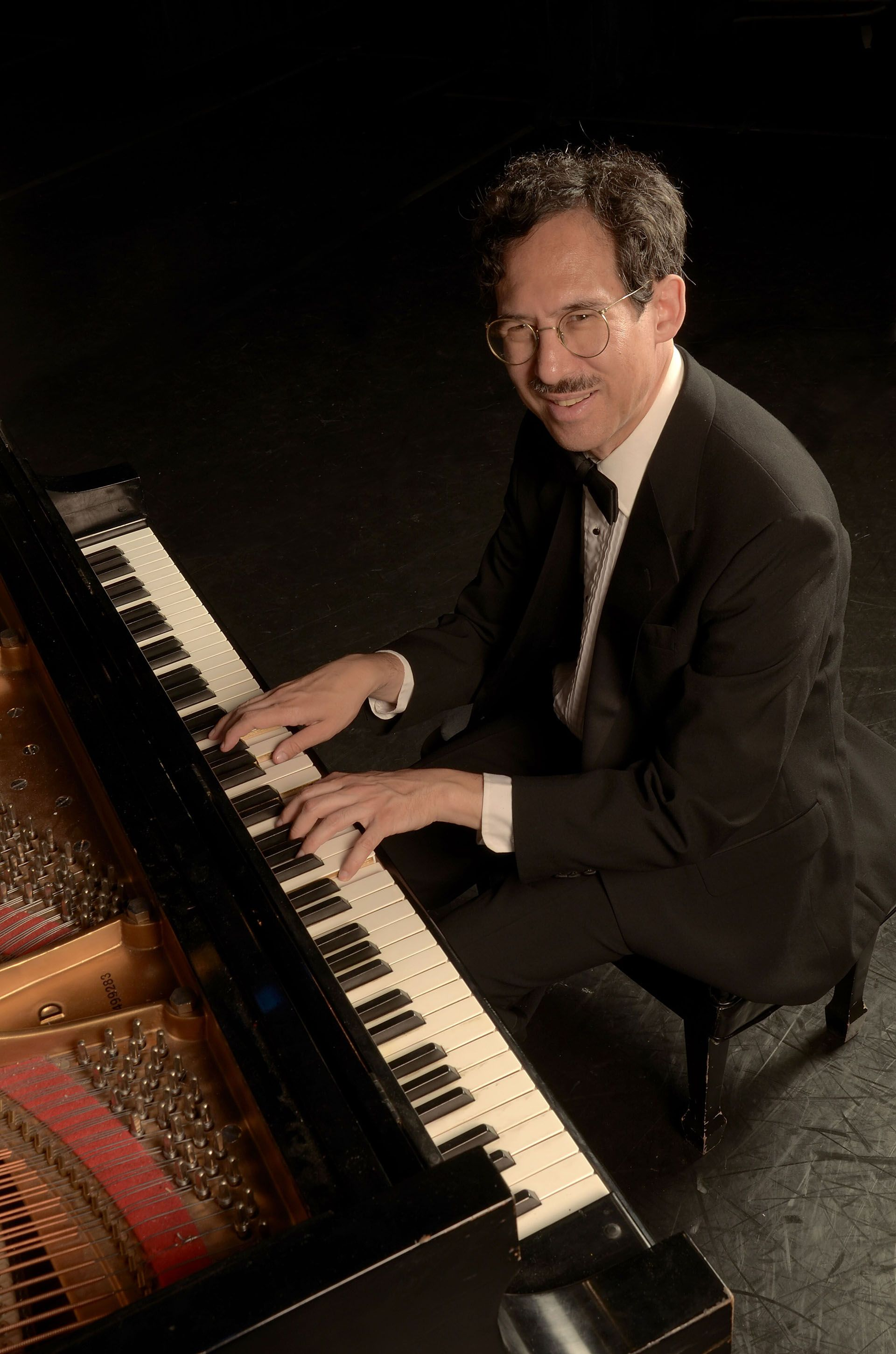 Michael Arnowitt wearing a tux and smiling while playing grand piano.